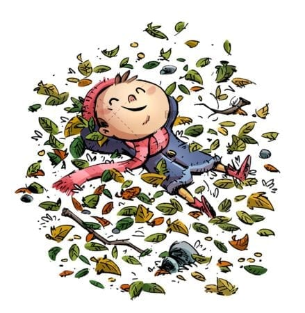 boy with hat and scarf lying surrounded by leaves isolated